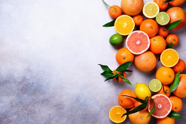 Frutas cítricas. surtido de cítricos frescos con hojas. naranja, pomelo, limón, lima, mandarina. vista superior