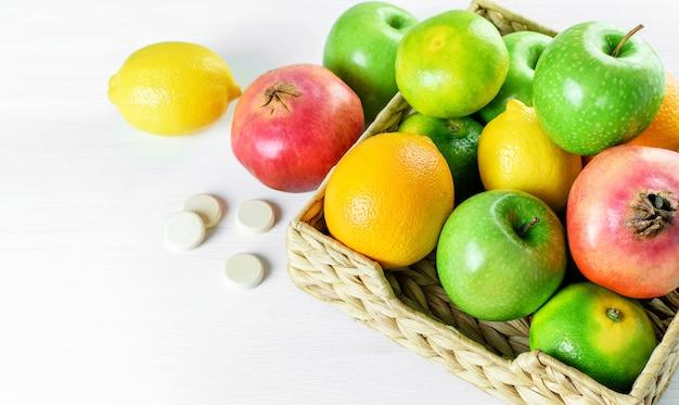Frutas cítricas tropicales en canasta de mimbre y pastillas blancas