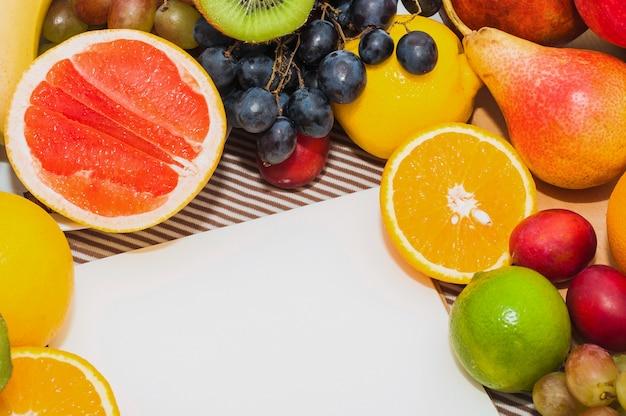 Frutas cítricas; uvas; peras; limón; con papel blanco en blanco