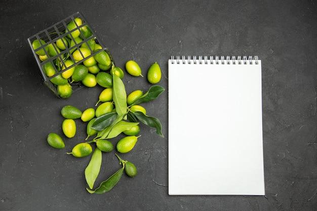 Frutas cítricos con hojas junto a la canasta y cuaderno blanco