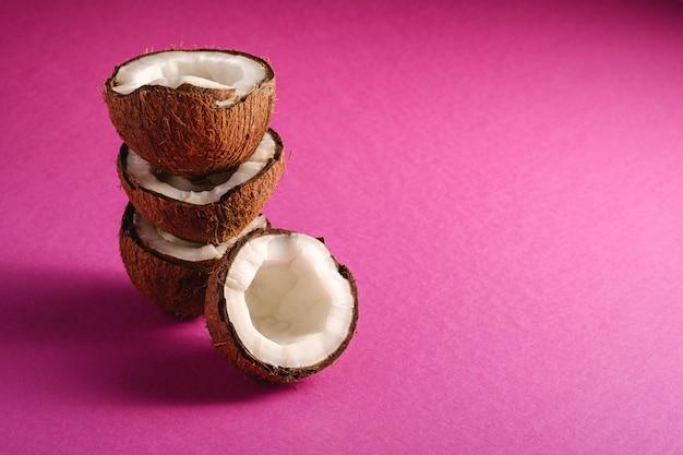 Frutas de coco apiladas sobre fondo liso rosa púrpura, concepto abstracto de alimentos tropicales, espacio de copia de vista de ángulo