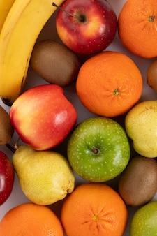 Frutas coloridas frescas maduras suaves jugosas enteras aislado en un piso blanco