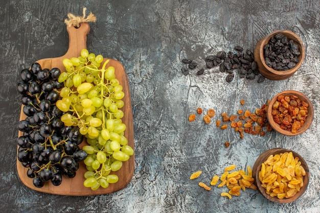 Frutas coloridas frutas secas uvas verdes y negras en la tabla de cortar