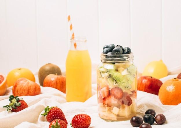 Frutas coloridas en un tarro junto a un batido de naranja.