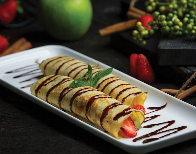 Frutas envueltas en crepes y salsa de chocolate.