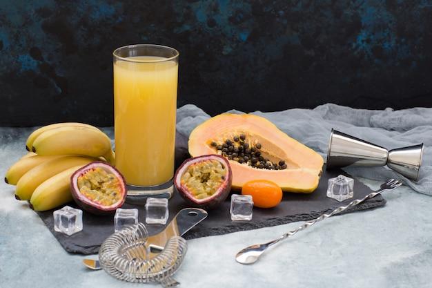 Frutas exóticas, cubitos de hielo, artículos para hacer cócteles alcohólicos y un vaso de jugo.