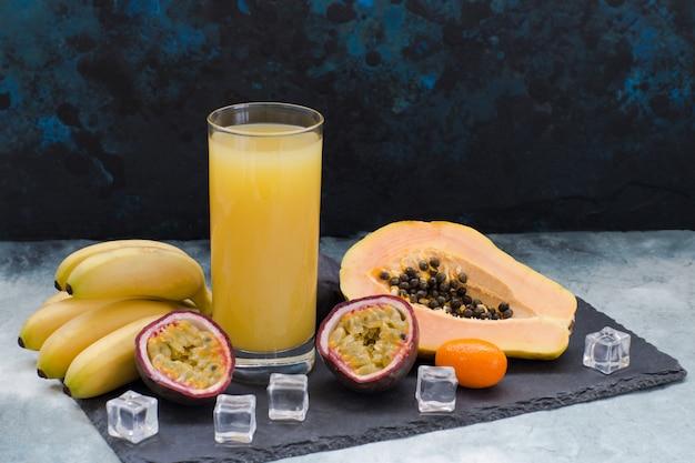 Frutas exóticas, cubitos de hielo y un vaso de jugo.