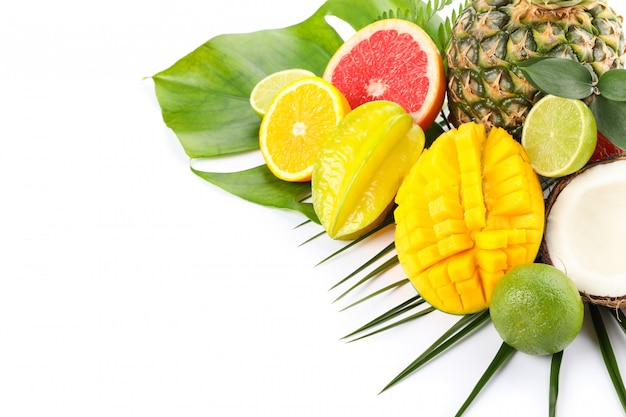 Frutas exóticas frescas y hojas de palma aisladas sobre fondo blanco.
