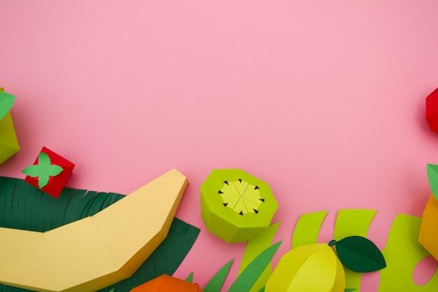 Frutas exóticas hechas de papel sobre fondo rosa