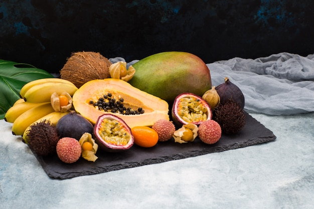 Frutas exóticas, hojas de monstera y gasas decorativas.