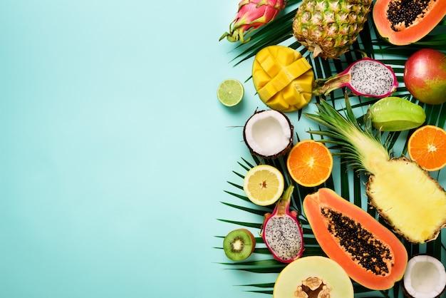 Frutas exóticas y hojas de palma tropical - papaya, mango, piña, plátano, carambola, fruta del dragón, kiwi, limón, naranja, melón, coco, lima.