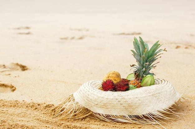 Frutas exóticas en un sombrero de paja cerca del océano.