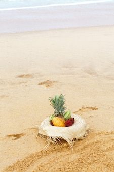 Frutas exóticas en un sombrero de paja junto al mar.