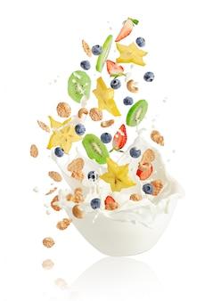 Frutas frescas, bayas, copos de maíz y nueces que caen en el recipiente con salpicaduras de leche