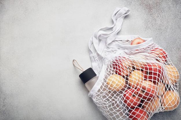 Frutas frescas y botella de agua en una bolsa de malla blanca ecológica