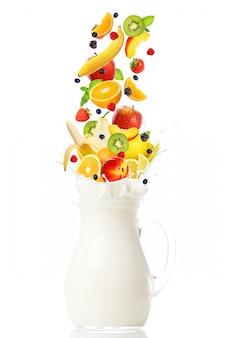 Frutas frescas cayendo en la jarra con leche