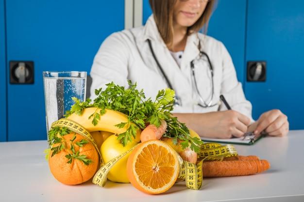 Frutas frescas con cinta métrica en frente de la escritura dietista femenina en el portapapeles