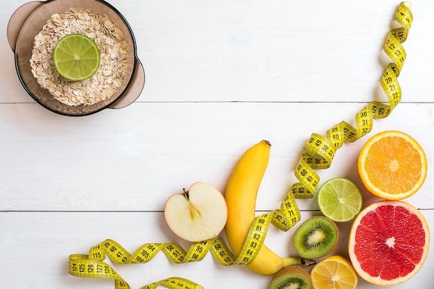 Frutas frescas con cinta métrica sobre fondo de madera blanca vista superior