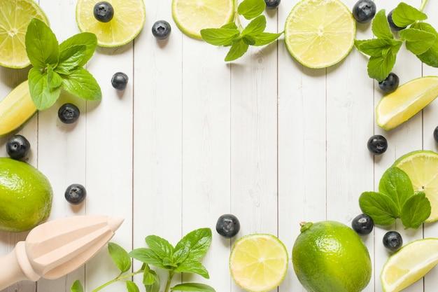 Frutas frescas cítricos lima menta arándanos sobre un fondo claro.
