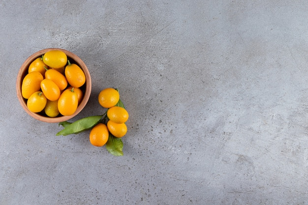 Frutas frescas cumquat cítricos enteros con hojas colocadas en un tazón de madera