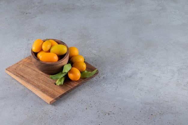 Frutas frescas cumquat cítricos enteros con hojas colocadas en un tazón