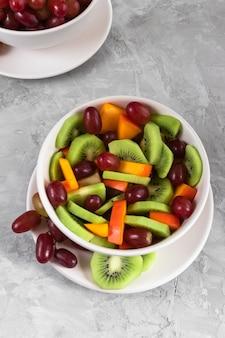 Frutas frescas en ensalada sobre el fondo gris