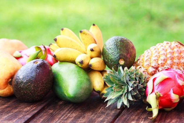 Frutas frescas. frutas exóticas mixtas sobre fondo de madera. alimentación saludable, dieta. vista superior con espacio de copia de hierba