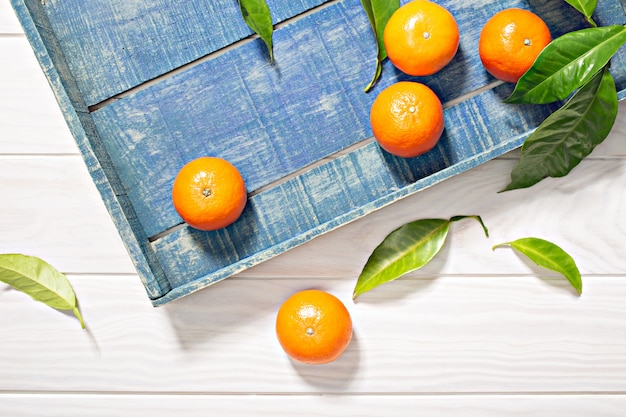 Frutas frescas de mandarina con hojas en cajón de madera