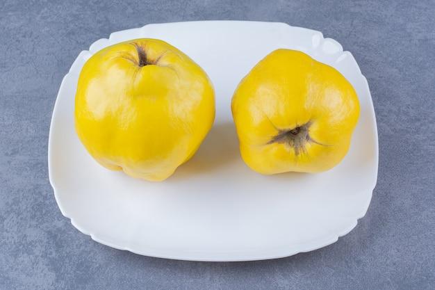 Frutas frescas de membrillo en placa sobre mesa de mármol.