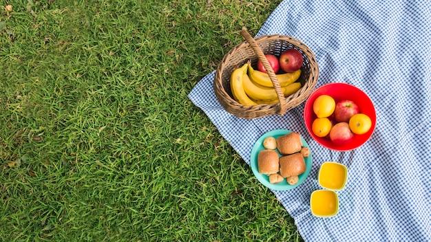 Frutas frescas; panes y vasos de jugo en manta sobre hierba verde