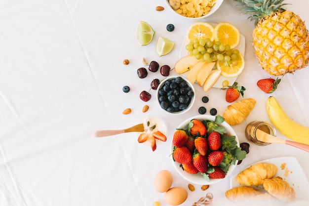 Frutas frescas saludables con huevo y croissant sobre fondo blanco