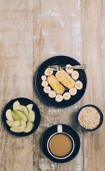 Frutas frescas saludables; taza de muesli y café sobre fondo de madera con textura