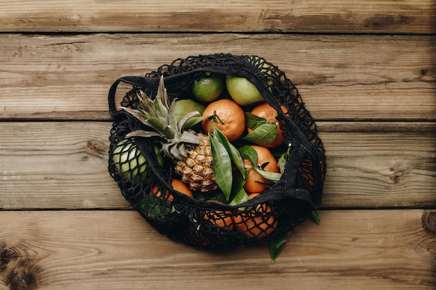 Frutas frescas de temporada mandarinas mandarinas con hojas verdes, manzanas verdes y piñas en bolsa de algodón ecológico