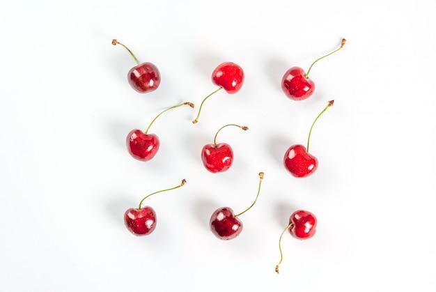 Frutas frescas de temporada orgánicas crudas. el patrón sin costuras, cerezas en un blanco. vista superior copyspace