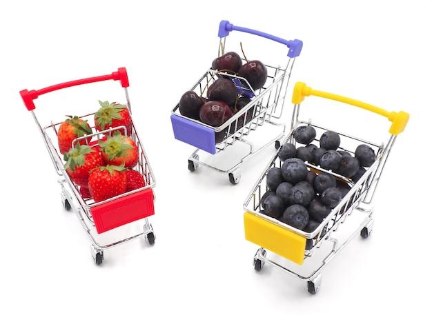 Frutas frescas del verano en el carro de la compra o la carretilla aislada en el fondo blanco.