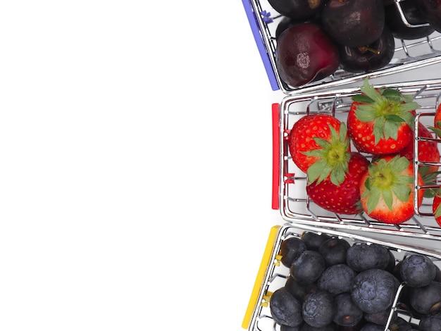 Frutas frescas del verano en el carro o la carretilla de compras aislado en el fondo blanco.