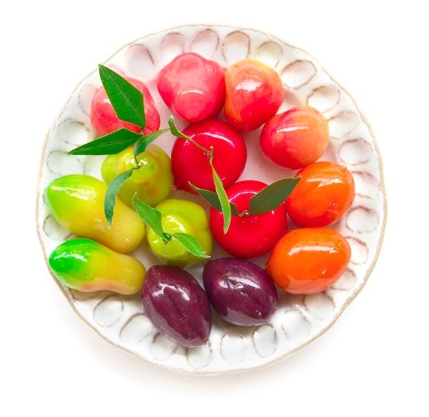 Frutas de imitación deletable del postre tailandés - kanom look choup hecho de frijol revuelto mezclado con azúcar y coco cubierto con jalea de vidrio vista superior aislada sobre fondo blanco
