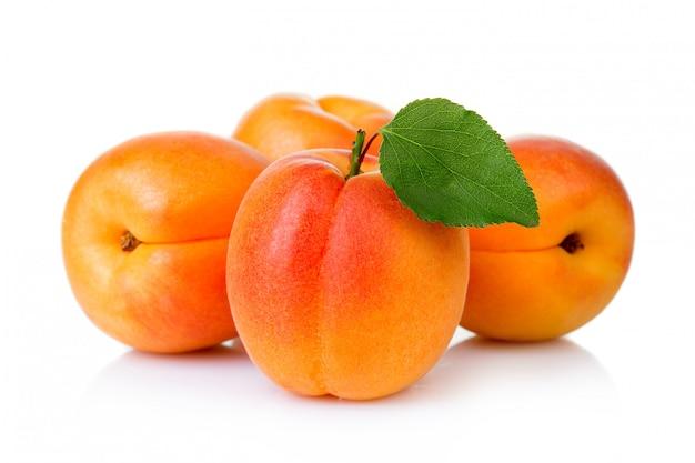 Frutas maduras del albaricoque con isolatet verde de la hoja en blanco