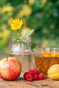 Frutas maduras de manzana, albaricoque y frambuesas, flor de caléndula con tallo en un frasco de vidrio y una taza de té verde sobre tablas de madera con fondo natural borroso