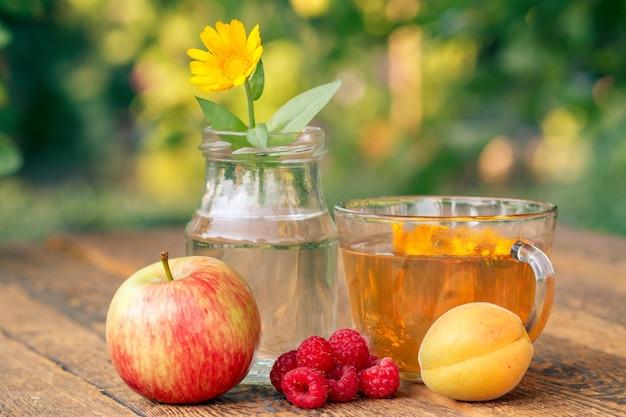 Frutas maduras de manzana, albaricoque y fresas, flor de caléndula con tallo en un frasco de vidrio y taza de té verde sobre tablas de madera con fondo natural borroso