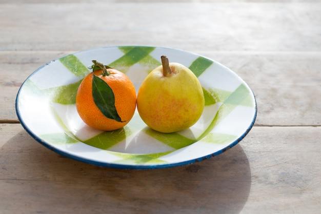 Frutas mandarina y pera en plato de porcelana vintage