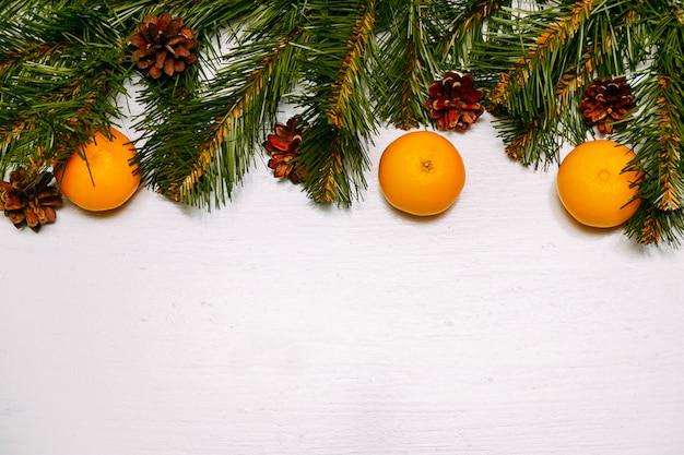 Frutas mandarinas y ramas sobre fondo de madera rústica