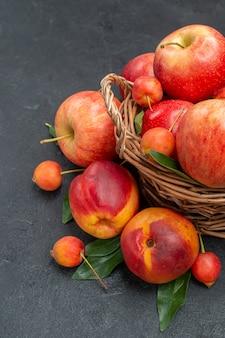 Frutas manzanas cerezas en la canasta nectarina con hojas