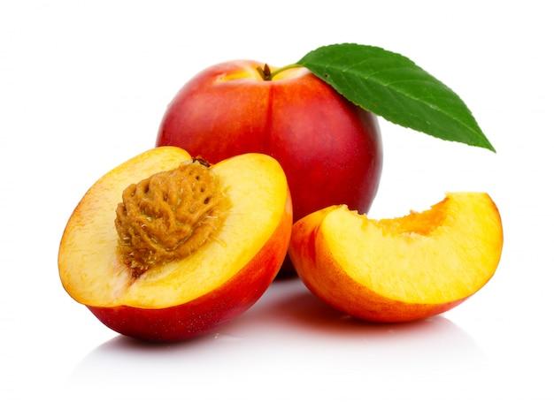 Frutas del melocotón con la rebanada y las hojas verdes aisladas