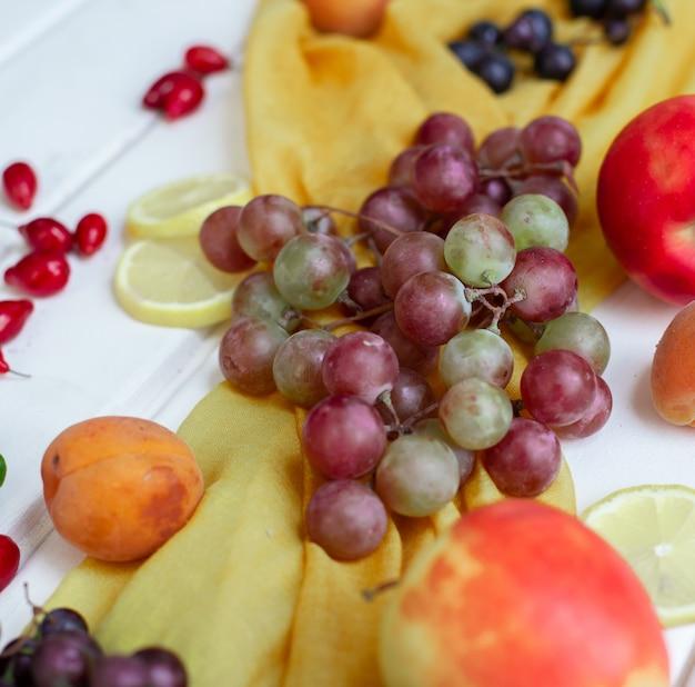 Frutas mixtas en una cinta amarilla sobre una mesa blanca.