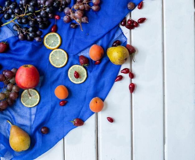 Frutas mixtas en una cinta azul sobre una mesa blanca.