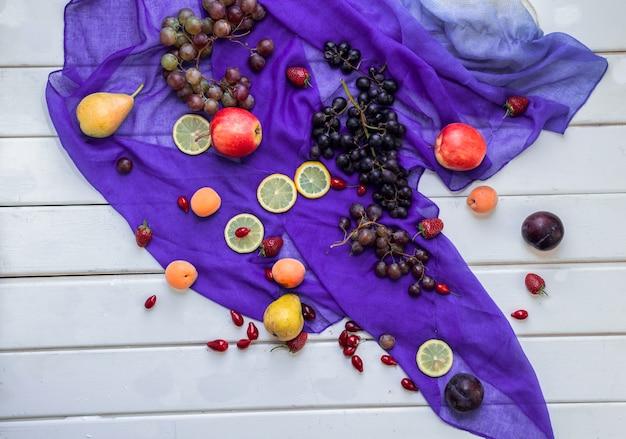 Frutas mixtas en una cinta violeta sobre una mesa blanca.