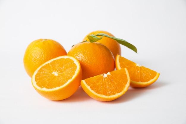 Frutas naranjas cortadas y enteras con hojas verdes