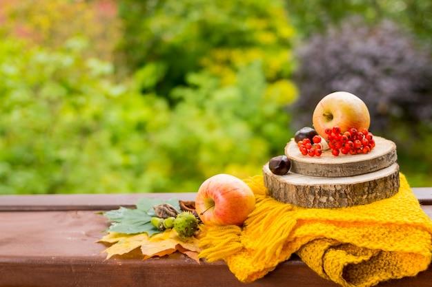 Frutas y nueces, bufanda amarilla sobre la mesa de madera