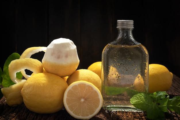 Frutas orgánicas frescas del limón con la botella de extracto de la cal en el fondo de madera de la tabla del vintage